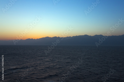 Sunrise over the Gulf of Aqaba with the sun still behind the mountains