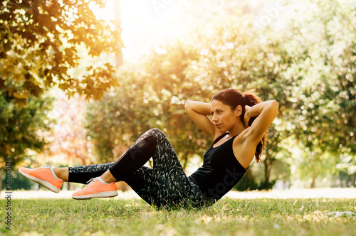 Sporty woman doing crunches workout in city park outdoor.