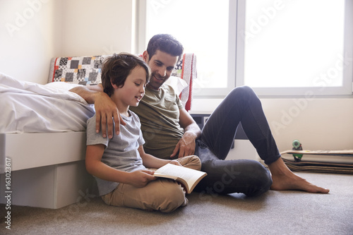 Father And Son Siting On Bedroom Floor Reading Book Together