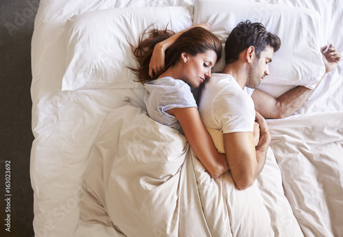 Overhead View Of Romantic Couple Lying In Bed Together