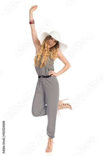 Happy Woman In Jumpsuit Is Standing On One Leg And Shouting
