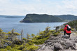 Young female tourist admiring calm bay in Newfoundland, Canada