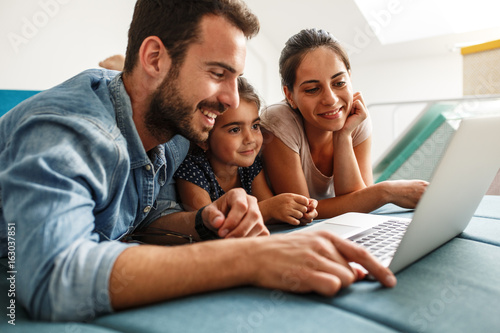 Happy family lies on bed and watching something on laptop.