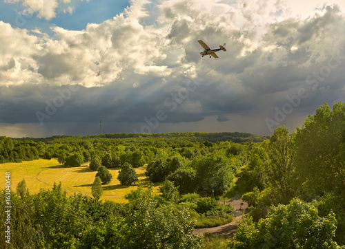 A view of the forests and field in the vicinity of Leipzig (Germany) and a small plane flying against the background of pre-threat clouds in the summer evening.