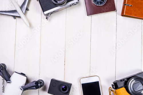 Travel accessories and gadgets with white wooden copy space in the middle