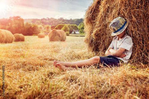 Boy leaning and sleeping against a haystack at sunset