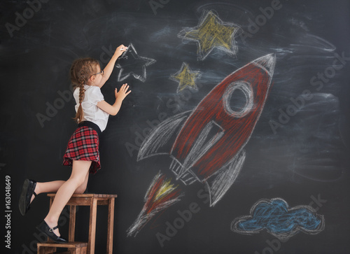 child drawing stars and rocket