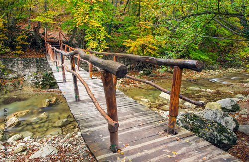 Wooden bridge in the autumn forest. Crossing the small river into The Grand Canyon of the Crimea