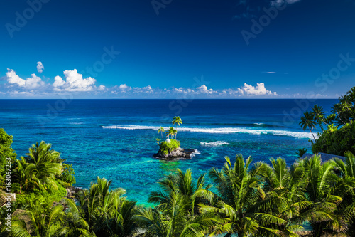 Tropical beach on Samoa Island with palm trees on small island, Upolu