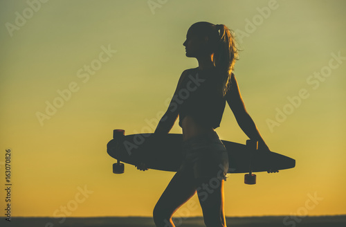 Silhouette of a beautiful, sexy hipster girl in tattoos standing with a longboard against the sunset at the sea