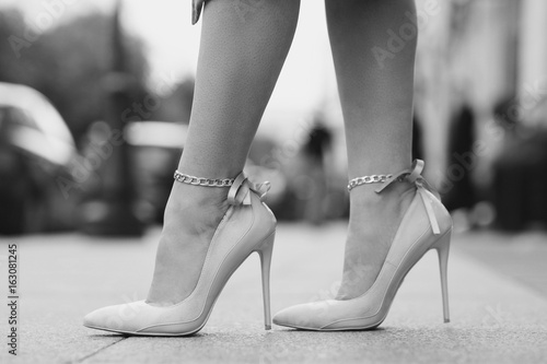 Woman walking down the street. Close up female legs wearing high heels