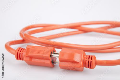 Bright orange extension cord on a white surface. Orange extension cable isolated on white background.