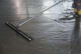 Worker leveling fresh poured concrete floor with a channel float - 163083270