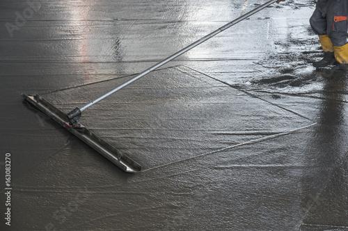Pracownik niweluje świeżo wylaną betonową podłogę z kanałowym pływakiem