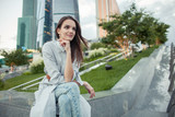 dreamy young attractive woman siting in green park in modern clean city with skyscrapers - 163085827