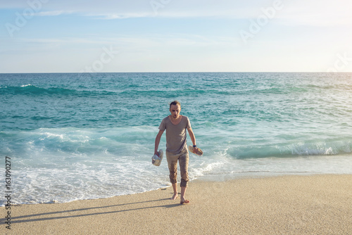 A young man walks barefoot from the sea along the shore in the sand leaving tracks and holds the sneakers