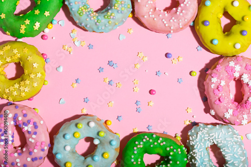 Colorful glazed donuts on a pink background