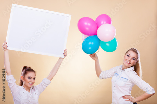 Two girls with blank board and balloons