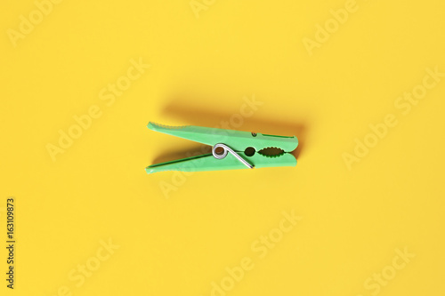 Green clothespin on yellow background