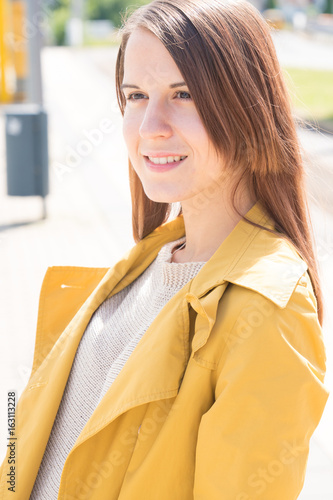 Young woman in a yellow raincoat waiting for a train at a railway station