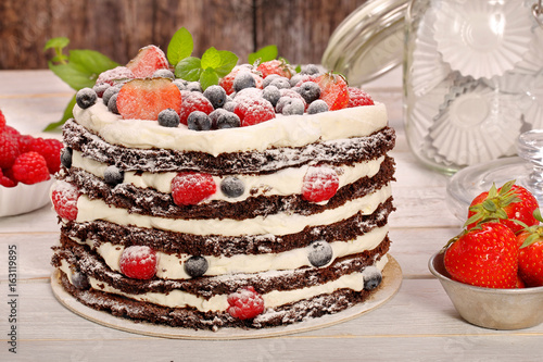 Chocolate cake with white cream and fresh fruits on wooden background