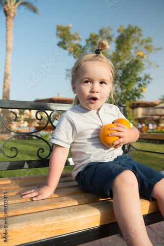 Amazed child sitting with two oranges on bench