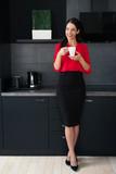 Beautiful young woman making coffee-tea in a modern kitchen  - 163132436
