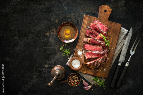 Sliced medium rare grilled beef ribeye steak - 163132899