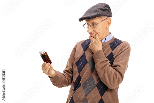 Confused senior looking at a bottle of pills