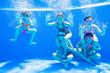 Leinwandbild Motiv little kids swimming  in pool  underwater.