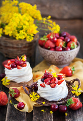 Delicious mini Pavlova meringue cake decorated with fresh berries