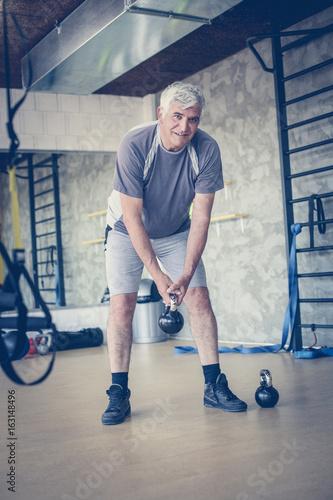 Active senior man lift weights at the gym. Looking at camera.