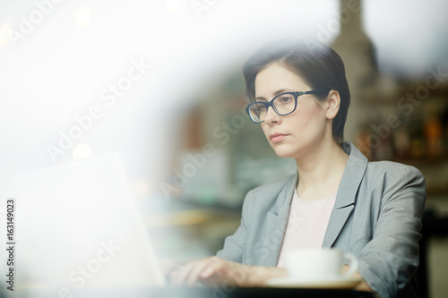 Serious analyst in front of laptop reading online information