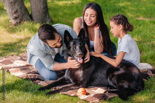 portrait of smiling family resting on blanket together with dog outdoors
