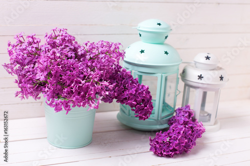 Poster Spring lilac flowers and bright turquoise  and white lanterns on white wooden background
