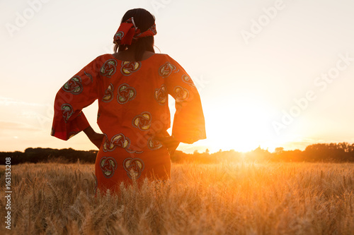 African woman in traditional clothes walking in a field of crops at sunset or sunrise