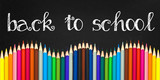 Fototapety Back to school written on a black board background with a wave of colorful wooden pencils