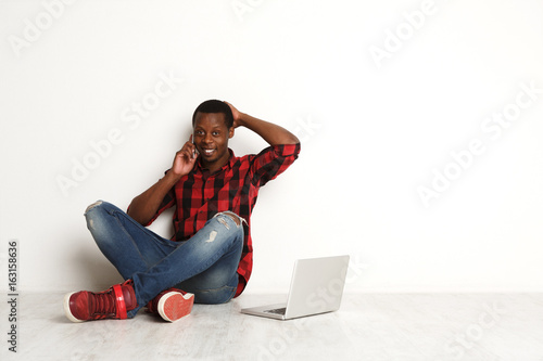 Happy black man using mobile and laptop sitting on the studio floor