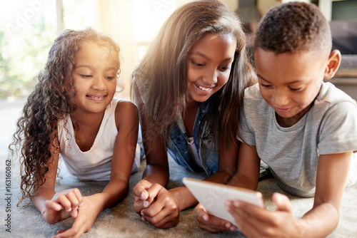 Cheerful black sisters and brother browsing tablet on floor