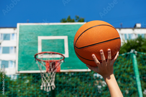 Hand with basketball on background of shield basket hoop