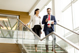 Young businesswoman and businessman walk down stairs in office with a tablet in his hand - 163167262