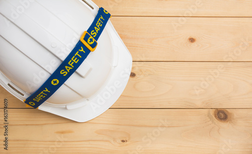 White plastic safety helmet on wooden desk with copy space.