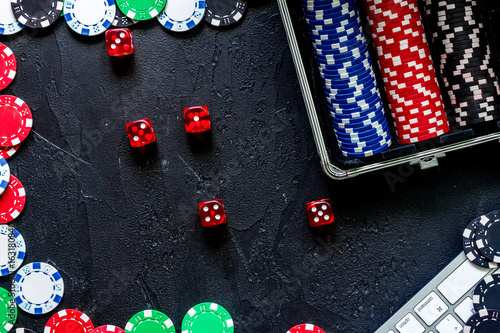 Poker set in a metallic case and keyboard on a grey table top view плакат