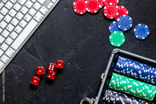 Poker set in a metallic case and keyboard on a grey table top view copyspace плакат