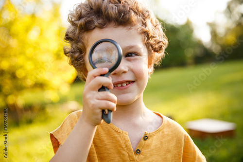 Young blonde boy playing with magnifier