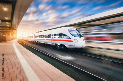 Biały nowożytny wysoki prędkość pociąg w ruchu na staci kolejowej przy zmierzchem. Pociąg na tory kolejowe z efekt rozmycia ruchu w Europie w wieczór. Peron. Krajobraz przemysłowy. Turystyka kolejowa