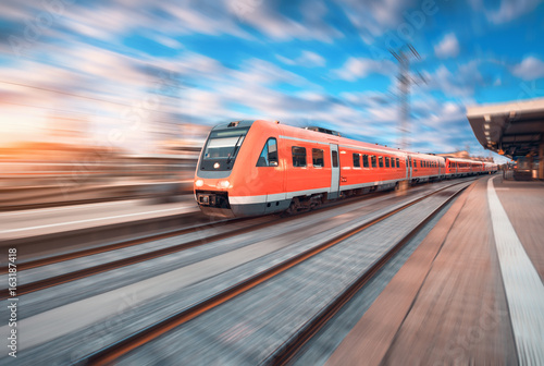 High speed commuter train in motion at the railway station at sunset in Europe Poster