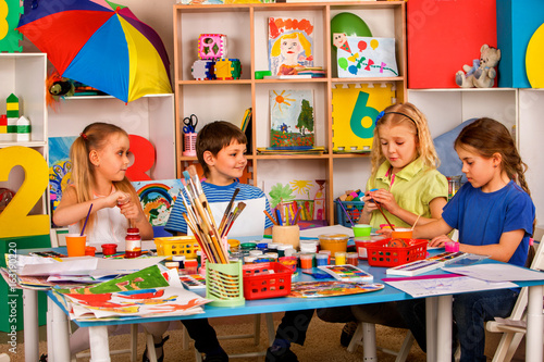 Small students painting in art school class. Children boy and girl drawing by paints on table. Portrait of kids in kindergarten. Children drawing in kindergarten. Independent children's creativity.