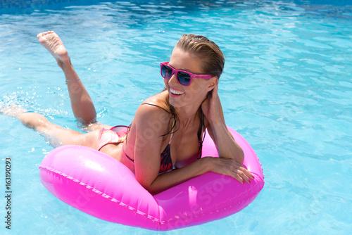 Frau mit Schwimmreifen im Pool