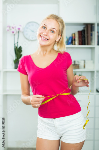 Girl standing with measuring tape